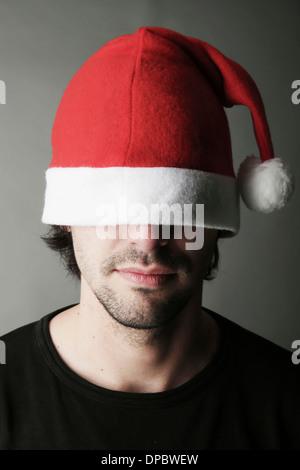 Young man wearing Santa hat, close-up - Stock Photo