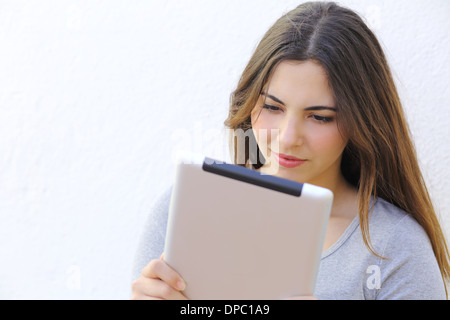 Portrait of a woman reading a tablet ebook on a white wall - Stock Photo
