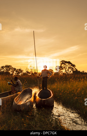 Native guides waiting in mekoro dugout canoes for tourists on safari as sun rises in Okavanga Delta, Botswana, Africa - Stock Photo