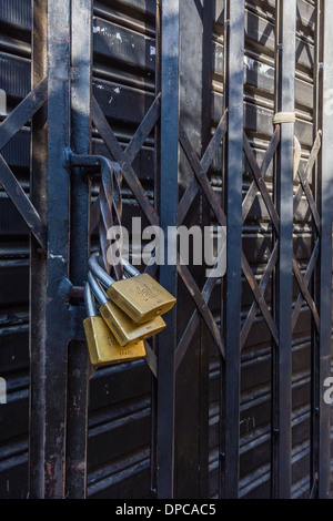Multiple padlocks secure a store's sliding metal gate in Sucre, Bolivia. - Stock Photo