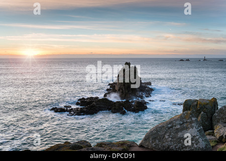 Rocky cliffs at Lands End in Cornwall with the Longships lighthouse in the distance - Stock Photo