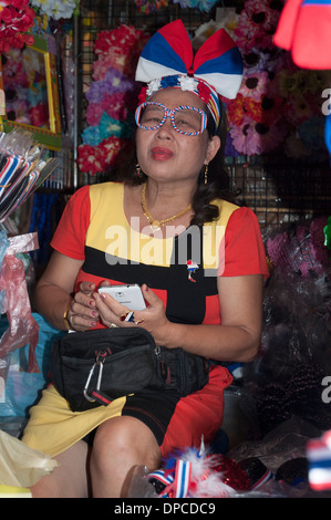 Stallholder wearing the colours of the government party associated with PM Yingluck Shinawatra, Bangkok - Stock Photo
