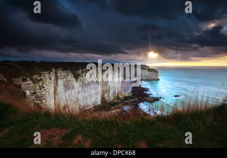 sunshine and storm sky over cliffs in ocean, Etretat, France - Stock Photo