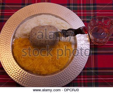 Burns supper Haggis Scottish, turnips, neeps, tatties, potatoes with whisky glass on tartan background Scotland - Stock Photo