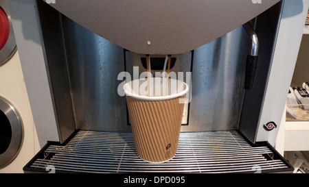 Drink dispenser pouring a disposable paper and plastic cup of coffee latte at Waitrose supermarket from a machine - Stock Photo