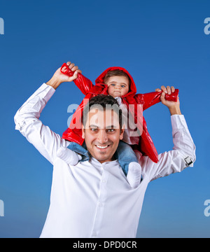Portrait of cheerful young father with cute little son sitting on his shoulders on blue clear shy background, having - Stock Photo