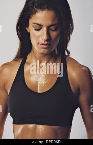 Portrait of middle eastern woman in sports bra with muscular body looking down against grey background. Female bodybuilder - Stock Photo