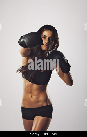 Portrait of a young woman boxer throwing a punch at camera while practicing on grey background. Mixed race female - Stock Photo