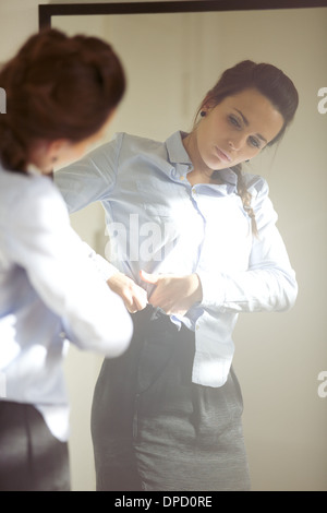 Beautiful young businesswoman wearing business attire in front of mirror. Young caucasian female model getting dressed - Stock Photo