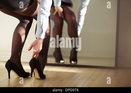 Closeup of female legs wearing high heels shoes. Woman adjusting high heels in front of mirror. - Stock Photo