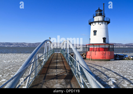 An extruded metal walkway leads to the Sleepy Hollow lighthouse on the icy Hudson River in Tarrytown, New York. - Stock Photo