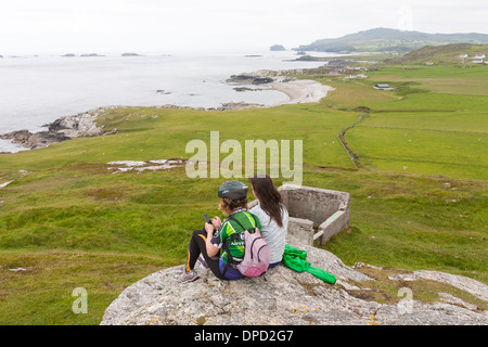 A brother and sister look at wildlife and coastal features and cliffs around Malin head on the most westerly point - Stock Photo