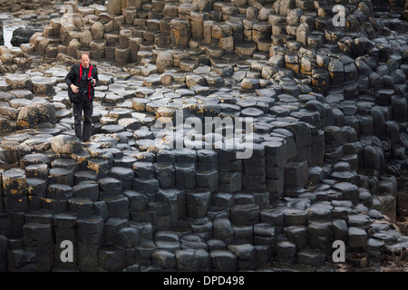 A photographer walks and climbs over stacks of basalt columns that make up the world famous Giants Causeway in County - Stock Photo