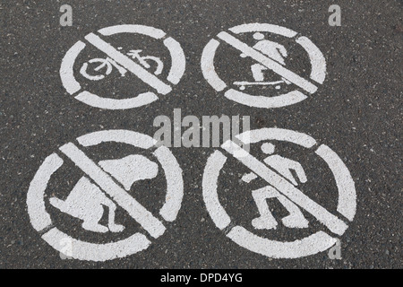 Do not do sign stenciled on a paved walking path. do not bike, skateboard, Rollerblade, and pick up after your dog. - Stock Photo