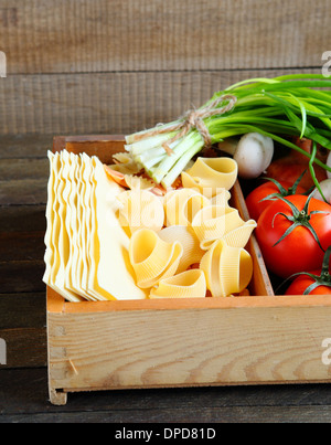 uncooked pasta in wooden box, food closeup - Stock Photo