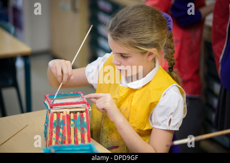 A girl in primary school in the UK making a model of a beach hut in an arts lesson. - Stock Photo