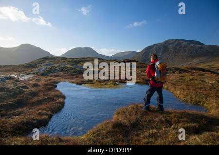 Walker beside a bog pool on a ridge high in the Twelve Bens, Connemara, County Galway, Ireland. - Stock Photo