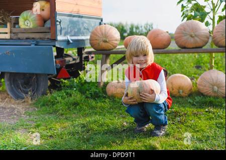 Little boy holding pumpkin - Stock Photo