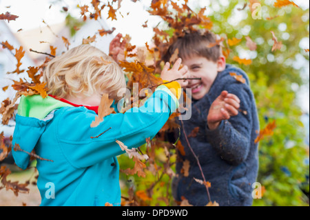 Two little boys throwing autumn leaves - Stock Photo