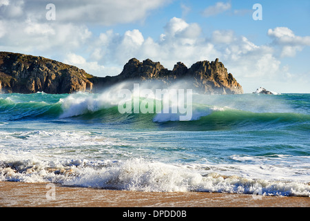 A curling wave breaking at Porthcurno beach, West Cornwall - Stock Photo
