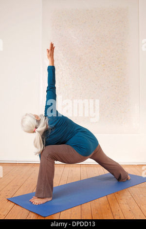 Germany, Dusseldorf, Senior woman practicing yoga - Stock Photo