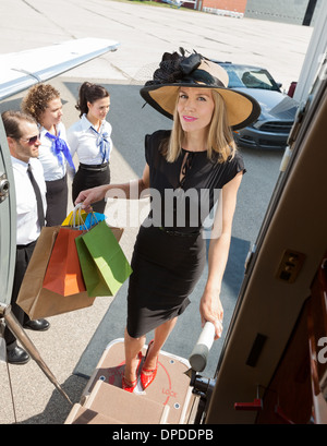 Confident Woman Carrying Shopping Bags While Boarding Private Je - Stock Photo