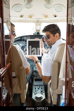 Pilots Using Digital Tablet In Cockpit - Stock Photo