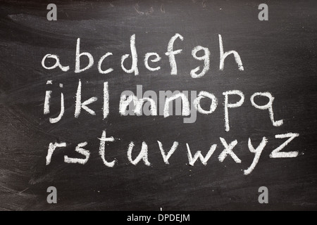 Handwritten letters of the alphabet written on a blackboard - Stock Photo