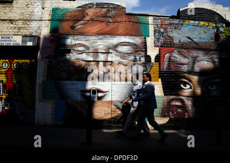 Two young Asian men walking past urban spray can graffiti street art Brick Lane area, East London E1 UK - Stock Photo