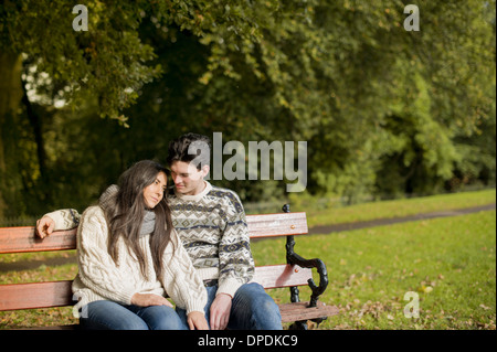Young couple sitting on park bench - Stock Photo