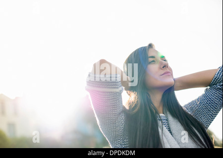 Young woman with hands behind head in sunlight - Stock Photo