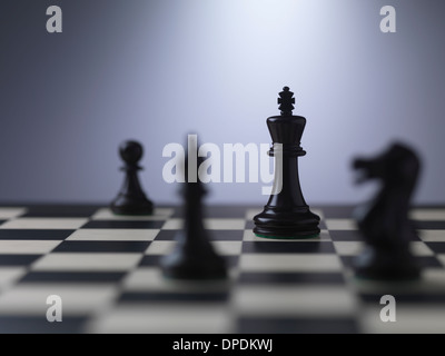Chess pieces on a board showing king - Stock Photo
