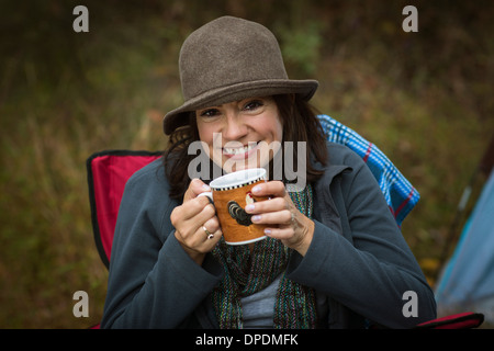 Mature woman sitting on camping chair, drinking hot drink - Stock Photo