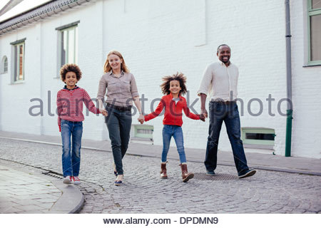 Parents and two children walking and holding hands on street - Stock Photo