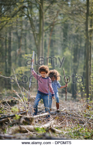 Brother and sister exploring together in woods - Stock Photo