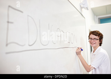 Portrait of schoolboy writing on white board - Stock Photo