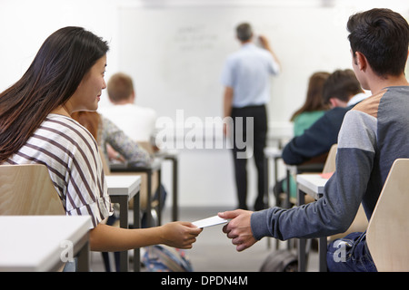 Teenagers passing secret note in class - Stock Photo