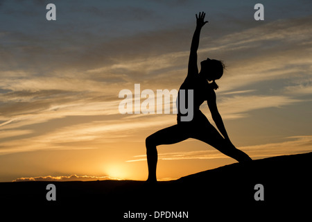 Silhouette of young woman doing yoga, Moab, Utah, USA - Stock Photo