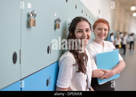 Portrait of teenage schoolgirls in corridor - Stock Photo