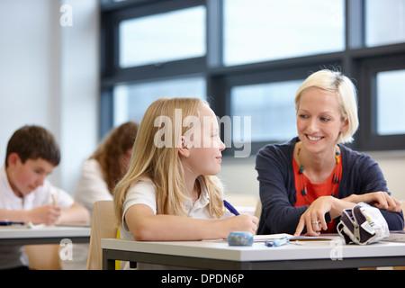 Teacher working with schoolgirl in classroom - Stock Photo