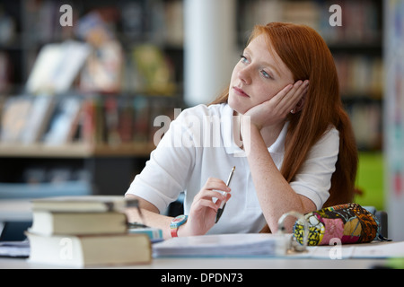 Portrait of teenage girl daydreaming in library Stock Photo