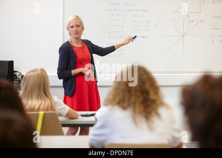 Female teacher using white board in front of class - Stock Photo