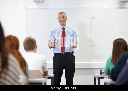 Mature male teacher in front of class - Stock Photo