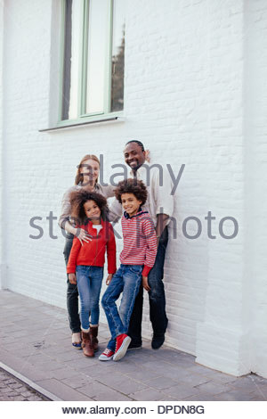 Portrait of parents and two children on sidewalk - Stock Photo