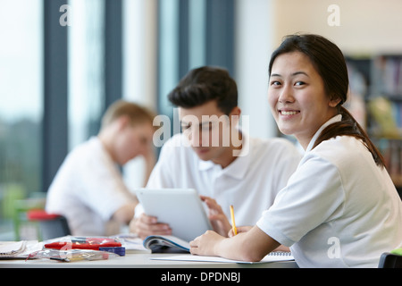 Teenagers working in school classroom - Stock Photo
