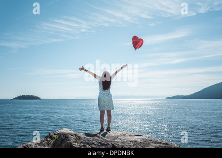 Mature woman arms outstretched with heart shaped balloon - Stock Photo