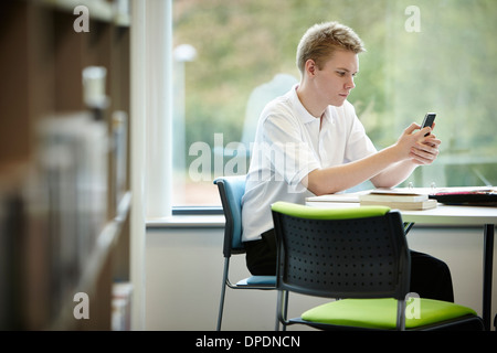 Teenage boy using cell phone in library - Stock Photo