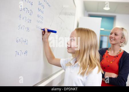 Schoolgirl doing multiplication on white board - Stock Photo