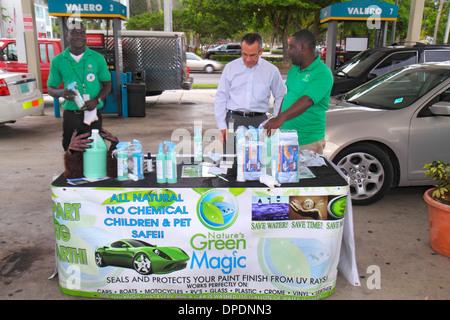 Miami Florida gas station petrol Black man salesman selling explaining Nature's Green Magic sealant UV rays protection - Stock Photo