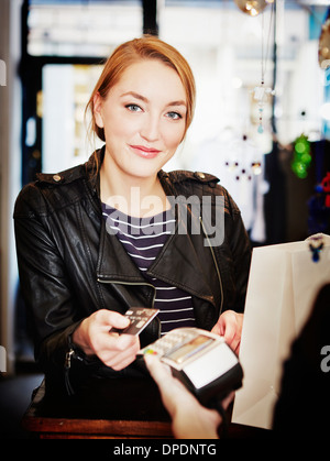 Young woman paying for shopping using credit card - Stock Photo